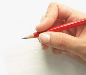 Hand holding a pencil and writing a novel